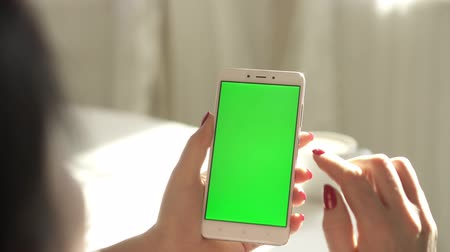 hromakey : Female hands hold the smartphone. Green screen. Hromakey. The woman has a red manicure.