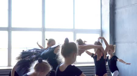 taniec towarzyski : Girl dancer in ballet school learns to dance. Little Ballerina in training in black dancing suit. Childrens ballet school.