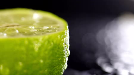 лимон : Patches of light of drops of water at a background. Drops of water fall on the cut lime on a black background. Limes Cut with Water Drops. Macro shooting of a citrus.