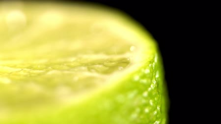 cítrico : Patches of light of drops of water at a background. Drops of water fall on the cut lime on a black background. Limes Cut with Water Drops. Macro shooting of a citrus.