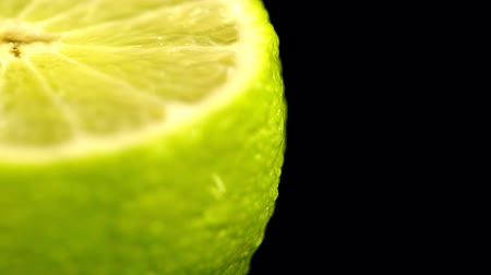bitter : Patches of light of drops of water at a background. Drops of water fall on the cut lime on a black background. Limes Cut with Water Drops. Macro shooting of a citrus.
