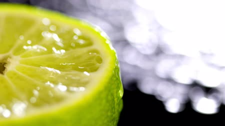 лимонный : Patches of light of drops of water at a background. Drops of water fall on the cut lime on a black background. Limes Cut with Water Drops. Macro shooting of a citrus.