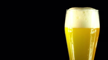 núpcias : Cold Light Beer in a glass with water drops. Craft Beer close up. Rotation 360 degrees. 4K UHD video 3840x2160.There are no people. Stock Footage