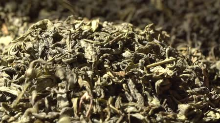 indian tea : SLOW MOTION: Tea leaves fall on a pile of a green tea - Macro shot. Stock Footage