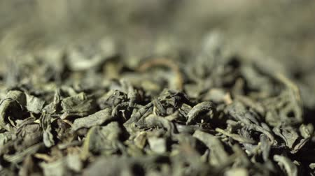 SLOW MOTION: Tea leaves fall on a pile of a green tea - Macro shot. Stock mozgókép