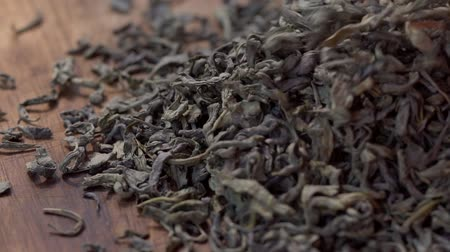 antioksidan : SLOW MOTION: Tea leaves fall on a pile of a green tea - Macro shot. Stok Video
