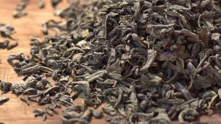 SLOW MOTION: Tea leaves fall on a pile of a green tea - Macro shot. Stock Footage