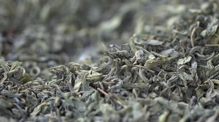 indian tea : Male hand picks tea leaves for brewing. Chinese green tea. Dried tea leaves background. Macro. Beautiful dried green tea leaves closeup