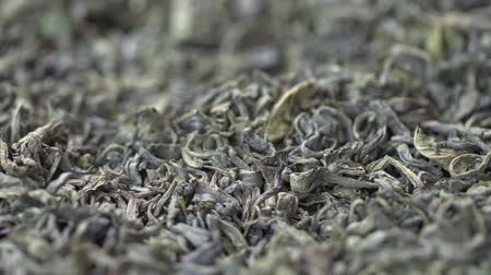 Female hand picks tea leaves for brewing. Chinese green tea. Dried tea leaves background. Macro. Beautiful dried green tea leaves closeup