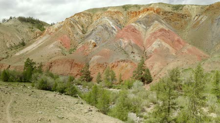 местность : Aerial rainbow mountain landscape in 4k. Drone footage showing the most beautiful valley in National Geopark, with sandstone hills covered by colorful pattern. Altai. Russia.