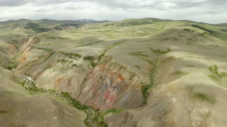 magas szög : Aerial rainbow mountain landscape in 4k. Drone footage showing the most beautiful valley in National Geopark, with sandstone hills covered by colorful pattern. Altai. Russia.