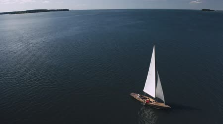 mastro : Aerial shooting of a sailing yacht in the sea. Sunny day at sea. Man and woman sailing on yacht at the sea Vídeos
