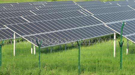 udržitelnost : Solar panels in a mountainous area near the road. Around the fence with barbed wire. Modern technologies.