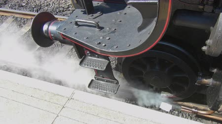 konzervált : A close up of a steam train as it lets off steam whilst paused at a station.