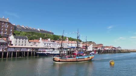 chegar : A tourist pleasure boat arrives in the North Yorkshire port of Whitby, Northern England. Vídeos
