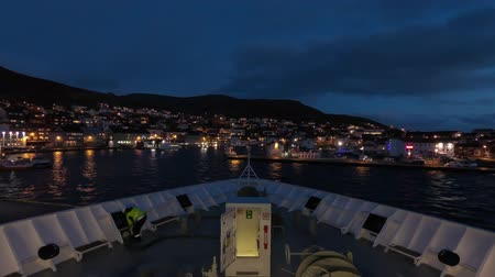 norvégia : A timelapse recording looking over the bow of a ship as it departs the city of Honningsvag, Norway. Stock mozgókép