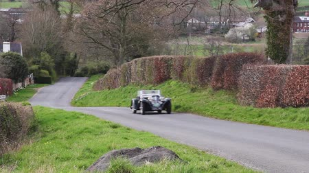 английский парк : A 1938 Aston Martin 1598 climbs Southwaite Hill in Cumbria, England.  The cars are taking part in the 11th Flying Scotsman Rally, a free public-event. Стоковые видеозаписи