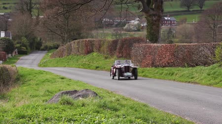 mg : A 1936 MG PB Tourer climbs Southwaite Hill in Cumbria, England.  The car is taking part in the 11th Flying Scotsman Rally, a free public-event. Stock Footage