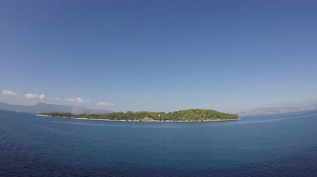 arborizado : A timelapse recording taken from a ship as it departs the port town of Corfu on the Greek island of Corfu.  The ship initially passes the tiny wooded island of Vidos.