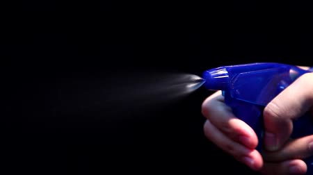 A person hand held pump sprayer on Black Background with Slow Motion