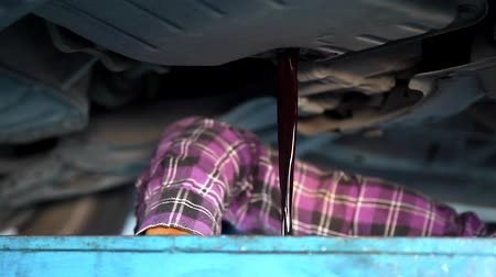 Auto Mechanic Draining Old Gear Oil Transaxle Underneath the Car Lift at the Garage
