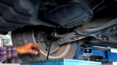 benzine : Auto Mechanic Draining Old Oil Underneath the Car Lift at the Garage