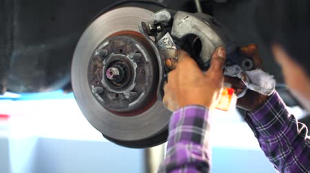 Auto Mechanic Repairing the Disc Brake Underneath the Car Lift at Garage Stok Video