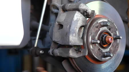 axle : Auto Mechanic Repairing the Disc Brake Underneath the Car Lift at Garage Stock Footage