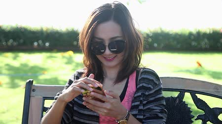 elküldés : Happy Young Woman Sitting in the Park and Using Smartphone Chat to Friend