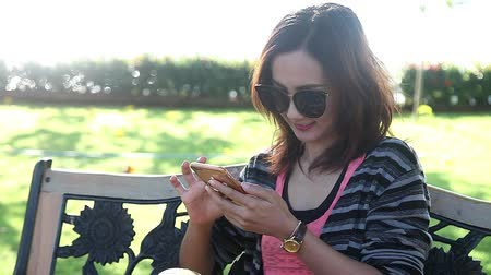 Happy Young Woman Sitting in the Park and Using Smartphone Chat to Friend