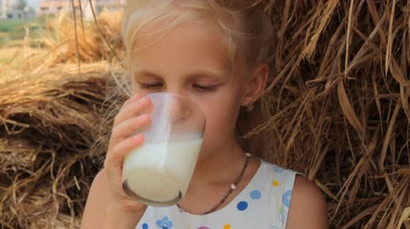 delicioso : Girl drinks cows milk from a glass against the backdrop of a haystack on a farm.