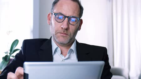 livro : Businessman working with tablet PC in his office or Hotel room while screen reflects in his glasses - tracking shot