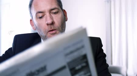 pausa : Businessman reading newspapers and drinks coffee, having a break in his office - tracking shot