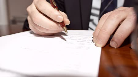 um : Businessman sitting at shiny office desk signing a contract with noble pen Stock Footage