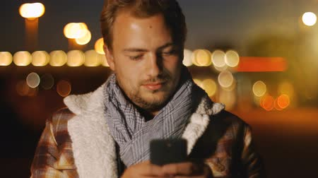 gündelik kıyafetler : 4K - Ultra HD - Handsome young man sms texting using app on smart phone at night in city. Using smartphone smiling happy wearing urban hipster outfit outdoors.