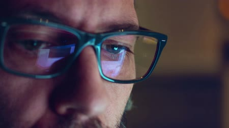 безопасность : Portrait of a mature adult man with glasses who works at night. Close up shot, display reflections