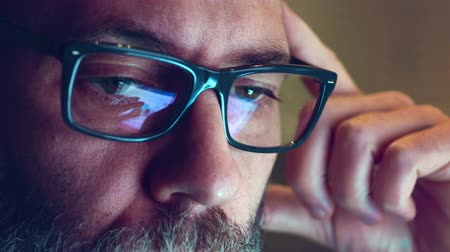bulva oční : Portrait of a mature adult man with glasses who works at night. Close up shot, display reflections