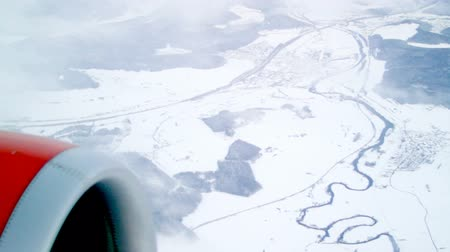 брезент : View out of plane an airplane on calm white snow winter landscape with clouds cross the