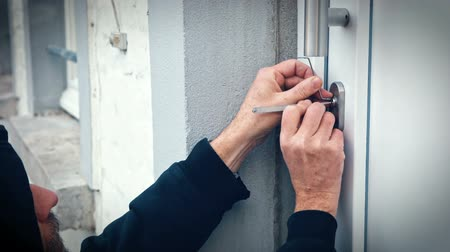 locksmith : intruder or burglar with lockpick tools open the front door to enter the house