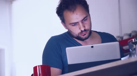 times : young man studying on tablet pc in home office kitchen Stock Footage