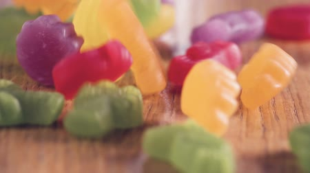 munch : Different colorful sweets on wooden table in slow motion close up. Looks like they are dancing and having fun. Stock Footage