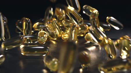 addiction recovery : Oil capsules on stone table with reflections. Close up and slow motion