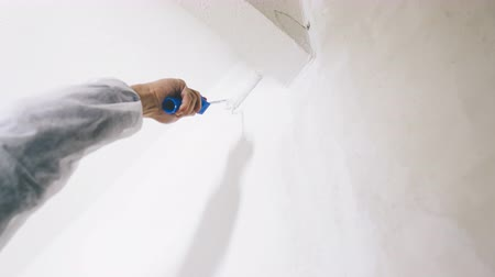 щеткой : Close-up of painter working with paint roller and brushes to paint the room in white colors. dig - do it yourself