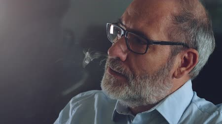 vaper : Confident well dressed man with beard vaping on electronic cigarette in his office