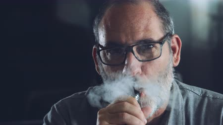 výrazy : Confident well dressed man with beard vaping on electronic cigarette in his office