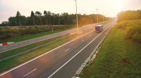 Commercial Truck with Cargo Trailer drives through empty Highway. Truck is White and blue. Sun shining in the background Stock Footage