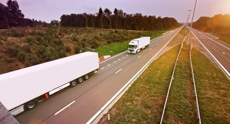Two similar commercial trucks with cargo trailers drives through empty highway. Truck is white. Sun shining in the background