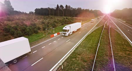 Commercial trucks with cargo trailers drives through empty highway. Sun shining in the background Stock Footage
