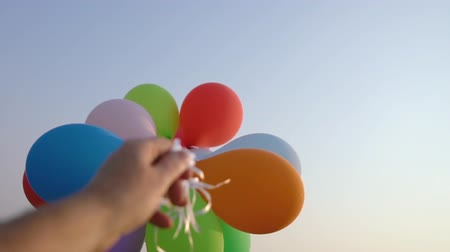 balão : lots of balloons against blue skies at sunset - slow motion shot