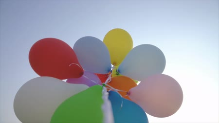 lots of balloons against blue skies at sunset - slow motion shot